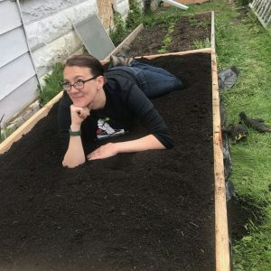 Christine Noelle laying in raised garden bed