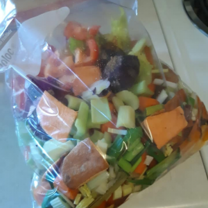 zip-loc bag full of veggie scraps such as onion ends, carrot skins, celery leaves, and more for making stock